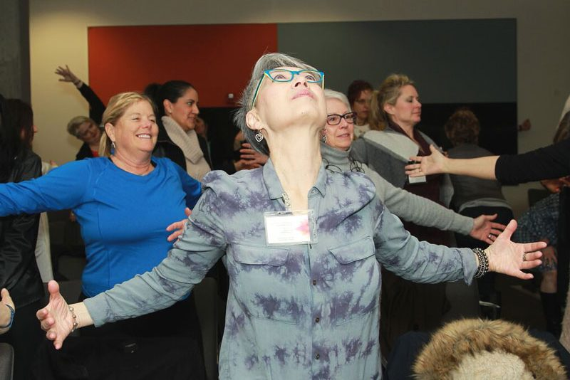 woman opening her heart during empowerment exercise at illuminating women spring conference